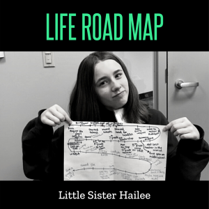 Little Sister Hailee holds up the paper where she has completed her Life Road Map. It winds from right to left and left to right on the paper, with lots of marks calling out life events in descriptive text.