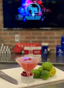 A martini glass filled with beautiful, cloudy pinkish/redish liquid and three fresh floating cranberries. The glass is on a counter with a cutting board containing limes, a knife, and a small bowl of fresh cranberries. Behind the counter and drink is a blurry tv screen with the Fire & Ice event logo.